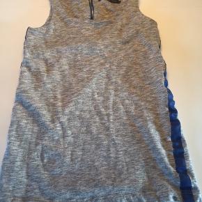 Meget kort, grå kjole i kraftigt materiale. M/bred blå stribe i begge sider og m/blå synlig lynlås på ryggen.  Længde: 68 cm.