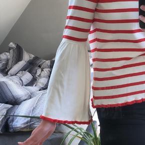 """Bluse med rund udskæring og """"trompet"""" ærmer. Rød/hvid stribet."""