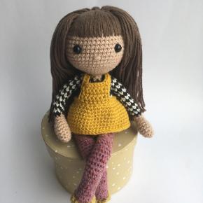Hæklet dukke med bøjelige arme og ben.