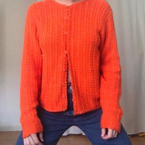 Cool orange cardigan i strik. Str S/M - kommer an på hvordan man vil have den skal sidde. Vintage.