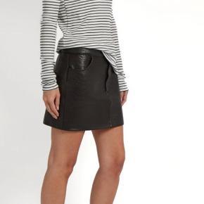 Mini pencil-nederdel i læder med flot struktur  Jeansmodel med lukning og lommer Mål: Længde 35, talje/liv 43 Størrelsen passer 40-42 Samme model som foto 2 og 3 Ingen brugstegn   Køb flere og få rabat - se profilside