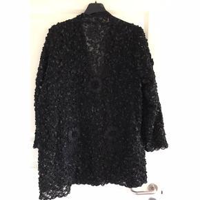 Smuk cardigan med flot struktur. Brystvidde: Variabel da den ikke skal lukkes, men ca. 75 cm. X 2. Længde: 85 cm.