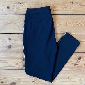"""Nye bukser fra Custommade i sorte med tynd, hvid stribe ned langs benene  Har aldrig været brugt, er kun blevet prøvet på og derefter vasket. Siden har de hængt i skabet  Modellen hedder """"Muno piping"""""""