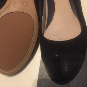 """Fine ballerinaer fra Clarks.  Størrelse 39,5.  Ruskind med """"lak"""" detaljer på snude og hæl.  Brugt max 3 gange da desværre er købt for små.   Kan sendes eller afhentes i Rødovre."""