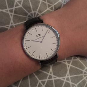 Daniel Wellington ur. Jeg købte selv uret brugt i år 2017. Jeg købte en ny rem i december 2017 (jeg har lagt et billede op af kvitteringen for remmen) og fik skiftet batteriet i foråret 2018. Det er oprindeligt et herreur, men kan sagtens bruges af kvinder (det har jeg selv gjort). Jeg har desuden en Daniel Wellington gaveæske til uret, og en original æske til remmen, som følger med ved køb.  Classic Bristol - 40 mm.  Der er en lille ridse i glasset, som allerede var der, da jeg købte det. Men det er uden betydning for funktionen.   Jeg sælger det, da jeg ønsker at købe uret i en mindre størrelse og en anden model.  Jeg sender gerne med DAO for 40 kr. oven i prisen.  (Nypris: 1495,-)