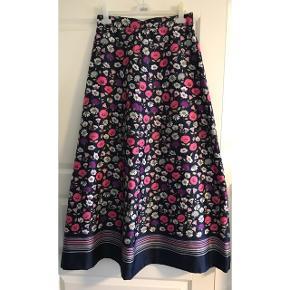 Lang nederdel i glat stof. A-form. Knaplukning og lynlås bagpå. Medfølger bælte/tørklæde. Livvidde: 39 cm. X 2. Længde: 103 cm.