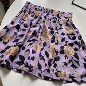 Super flot nederdel i pastel lilla med blomstermønster. Elastik i talje og med læg.  Sælger nederdel i str 36 og blusen i str 42.  Som ny.  100% viskose.