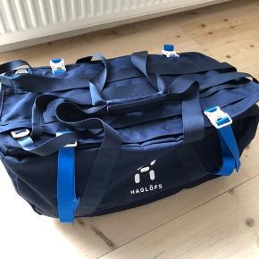 Model Cargo 60.   Let og alsidig duffelbag, der nemt kan pakkes væk uden at fylde alverden.  Tasken har ét stort hovedrum – og øverst er der yderligere et aflangt rum, som kan udvides opad en hel del, når der er brug for ekstra meget plads.  Endvidere er der mulighed for at fastgøre ting udenpå tasken ved hjælp at de to praktiske stropper, der er syet fast øverst på tasken i hele længderetningen.  Tasken kan bæres på 3 forskellige måder – med skulderstropperne gemt væk, når de ikke er i brug.  Duffelbag'en har kompressionsstropper på begge sider – og solide bærehåndtag i enderne.