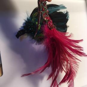 To smukke hårspænder med fjer og perler/pailletter. Den ene med petroleumsfarvede fjer og perler og den anden med pink fjer og pailletter. Længde ca. 16cm. 50kr Kan hentes Kbh V eller sendes for 40kr DAO