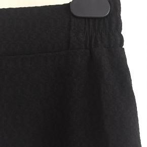 Fin nederdel fra Neo Noir. Længde under knæet. Elastik i taljen. Sort med diskret struktur i stoffet. Aldrig brugt. Str XS, passer XS-S. Kan afhentes/leveres i Aarhus eller sendes efter aftale.