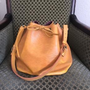 Louis Vuitton Petit Noe vintage taske med lilla for. Der er tegn på slid da det er et vintage item. Lysning af farve i kanten i bunden og lidt rundt omkring, fremstår generelt rigtig pænt og ser ud som på billederne. Har ikke kvit eller dustbag. Tasken er købt vintage, dog kan jeg sende billeder af serienr og hardware, den er selvfølgelig ægte. De går ofte for i omegnen af 6000 på brugt sidde da der ikke er mange tilbage med det lilla for. Prisen er fast, tasken kan sendes eller afhentes i indre KbH. Mængderabat ved køb af flere items på min shop.