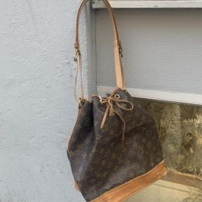 """Vintage Louis Vuitton model """"Noe GM"""" af monogram kanvas.  Tasken fremstår i flot velholdt vintage stand, med en naturlig patina på kernelæderet og brugsspor på hjørnerne.  Stroppen på tasken er blevet restaureret.  Tasken måler ca 31x26cm."""