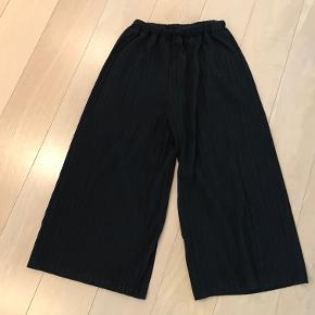 Smarte bukser med stor svaj og stoffet er rillet.