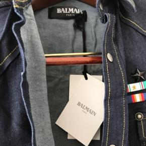 Enestående, ikonisk og helt ny Balmain skjorte. Har haft den hængende i skabet i et længere stykke tid nu og er simpelthen blevet for bred til den. Skjorten er S. Den er købt i Balmain butikken i Paris og kostede godt 7.399kr. Lavet i Paris. Kan også benyttes af en medium (M) bliver slim.