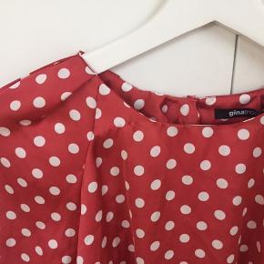 Så glad prikket skjortebluse fra Gina i brændt orange, med lidt fine læg ved halsen og lille åben dråbelukning bag på.
