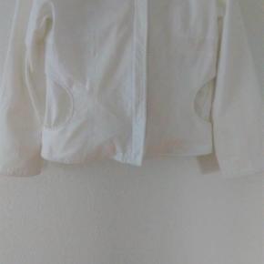 """Brand: St. Martins Varetype: Super fin feminin jakke med detaljer Farve: hvid  Super fin feminin jakke fra St. Martins. Str L. To lommer foran. To lommer indvendigt med fint mønstret kantebånd. Shell: 100% bomuld. Linning: 70% bomuld og 30% polyester. Der står indeni at den skal renses, men jeg har vasket den i Neutral uden problemer.  Bytter ikke. Måler ca 51 cm fra armhule til armhule. Måler ca 47 cm ved livet. Måler ca 52 cm nederst vandret. Og ca 59 cm fra skulderen og ned. Ved ikke om den skal stå under - næsten som ny. Eller god men brugt. Har kun haft den på få gange.  100 pp. Bemærk lille lidt mørkere """"plet"""" mellem lommen og lynlåsen. Tror den er købt med den. Måske indvendigt iforet."""