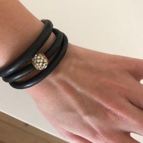 Super flot armbånd i læder fra Hultquist med guld detaljer. Passer de fleste, da du skal kan bestemme for mange gange den skal rundt om armen.   Brugt meget lidt.