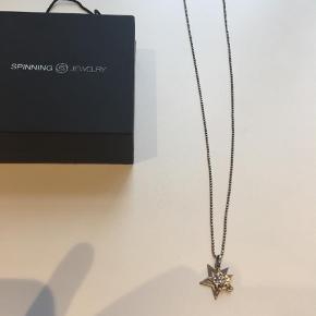 Varetype: Halskæde Størrelse: Halskæde Farve: Sølv  Flot Spinning Jewelry halskæde i fin længde. Smukt stjerne vedhæng med smukke funklende zirkoner.  Kommer i den flotte gaveæske.  Nypris var 899.  Mindstepris kr 250+