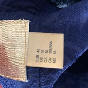 Smuk nederdel i A-form. Aldrig brugt men uden prismærke. Nederdelen er foldet om på billedet for at hænge ordentligt. Lynlås i siden. Livvidde 90 cm, længde 81 cm.