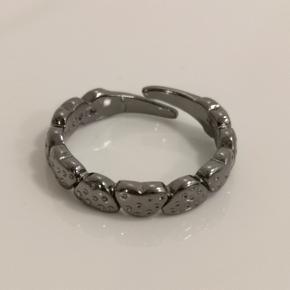 Simpel sort pilgrim ring med hjerter. Den er justerbar.