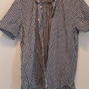 L.O.G.G kortærmet skjorte i str. L. Skjorten har en lomme på brystet. Stoffet er ternet hvidt og blåt og er i bomuld.