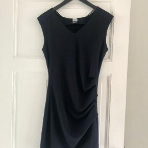 Kjole fra Saint Tropez i str. S. Kjolen er mørk mørkeblå. Stoffet er lavet i en viskose-blanding og er elastisk i stoffet, så den former sig efter kroppen. Kjolen har rynkeeffekt i taljen og skjult lynlås i siden.   Kan sendes eller hentes i Kbh 😊