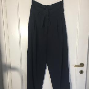 Højtaljet bukser fra COS med fint bindebånd i taljen og vide ben. Har kun brugt dem 2-3 gange.