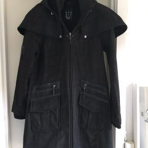 Superlækker og helt ubrugt softshell frakke. Med flotte skinddetaljer , flot præget stof, og meget velsiddende . Med dobbelt lynlås og aftagelig hætte