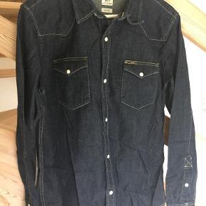 Skjorte fra Lee i mørk demin. Modellen hedder Western Shirt og har de fineste trykknapper.