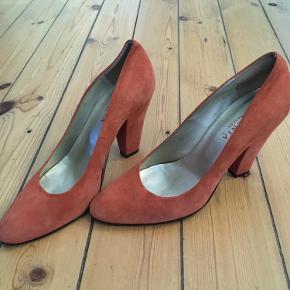Super flotte heels stiletter i ruskind fra Gardenia i en varm orange farve. Jeg har købt dem herinde, men de passer desværre ikke til det, jeg havde regnet med, så de sælges billigt.