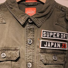 Fed kortærmet skjorte fra SuperDry.  Man kan sætte eget navn på med velcro på brystet.  Aldrig blevet brugt.  Skriv hvis du er interesseret i flere af mine ting.