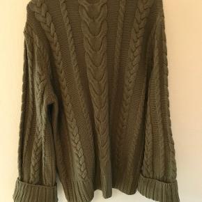 Skøn kabelsweater i ren bomuld. Der er to slidser i siden forneden med knapper, og ærmerne har stor vidde forneden. Sweateren er købt for stor og derfor aldrig brugt.