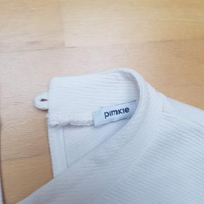 Råhvid top fra mærket Pimkie, købt i Spanien. Kraftigt stof med tekstur og fine detaljer som høj hals og knaplukning i ryggen. 100% polyester.