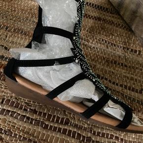 Nok sommerens fedeste sandal. Total skinnende. Får masser af opmærksomhed. Sandalen er blød og med super lækker komfort. Farven er sort.  Nye og ubrugte.