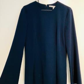 Rigtig pæn faconsyet bluse i mørkeblå. På ryggen går lynlåsen hele vejen ned.