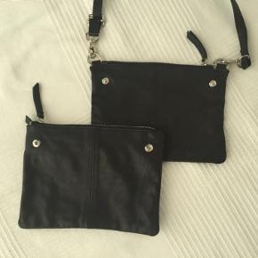 Varetype: Crossbody i skind. Dobbelttaske. Størrelse: 21 x 16. Rem 130 Farve: Sort Oprindelig købspris: 800 kr.  Tasken er speciel ved, at den kan deles i to, alt efter behov.