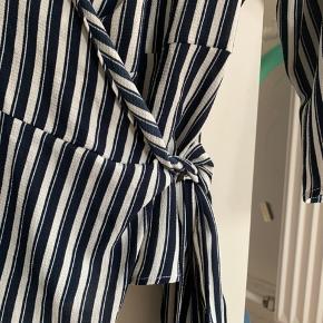 Fin wrap bluse med blå/hvide striber, 3/4 ærmer og bindebånd i taljen.   Tags: slå om, slå-om