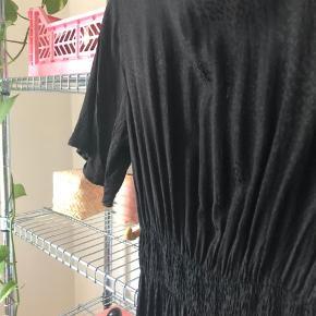 Flot kjole med fint leoprint, som giver lidt spil i det sorte stof. Den går mig til midt på skinnebenene.