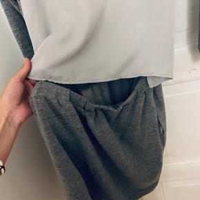 Fed grå kjole i blødt stof. Den har elastik i taljen og en fed detalje bagpå, men tyndt stof og hul så man kan se et stykke af ryggen