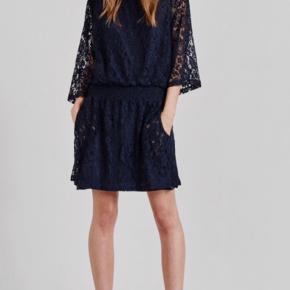 - fin blonde kjole med elastik i taljen - 3/4 ærmer  - lommer i   Brystmål:104 cm rundt - skal sidde løst  Længde: 98 cm  Talje: 80 cm rundt +- pga slå om