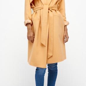 Lækker frakke. Kan sagtens bruges som vinterjakke med en trøje under. Har haft samme model før.  Har aldrig været brugt.  Samme model kan stadig fås i Magasin.    Frakke Farve: Fersken/ Nektar Oprindelig købspris: 2200 kr.
