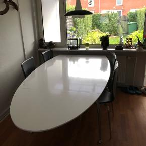 Lækkert ovalt spisebord med plads til 4 stole i nedslået stand og 8 personer med begge plader slået ud.Højglans med stålben.  To meget små skader og en overfladisk lille rids, som nemt kan dækkes, ellers som ny. (Billede tilføjet i kommentar feltet)