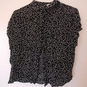 T-shirt/top med prikker fra H&M. Brugt få gange. Har lille slids i hver side. Er behagelig og let at have på.  Kan afhentes i Aarhus eller sendes.