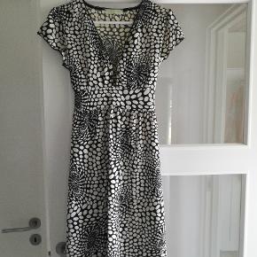 Super sød knælang kjole sort/hvid mønster med bindebånd under barmen der giver virkelig fin pasform.