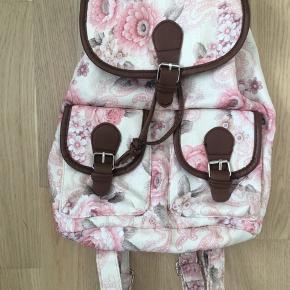 Fin lille rygsæk / turtaske med magnetlukning. Der er to lommer foran og en lille lomme med lynlås indeni. Justerbare stropper. Blomstret med brune kanter. Aldrig brugt.