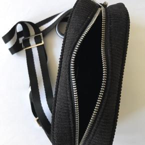Denne klassiske Becksöndergaard cross-body taske er en tidsløs taske. Tasken kan fungere til hverdag såvel som specielle begivenheder med taskens fine fløjl materiale. Med taskens aftagelige remme er det muligt at skifte til andre remme og ændre stilen på tasken. Tasken har derudover en lille inderlomme, så du altid kan holde styr på dine mindre ejendele. – Størrelse: 13,5×19 – Justerbar og aftagelig rem – Indvendig foret