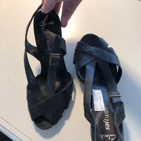 Varetype: Heels Størrelse: 7 Farve: Sort Prisen angivet er inklusiv forsendelse.  Clarks software sandal, så skønne at have på Får desværre ikke brugt dem, de er helt ubrugte Ny pris 700kr Hælen er tyk og 9 cm høj Indvendigt mål 25,5-26