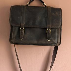 Lækker lædertaske fra Velorbis. Den er ca 2 år gammel og vil stå endnu flottere efter en gang læderfedt!  Den er ca 32 cm høj 44 cm bred og 12 cm dyb. Den har to lommer udvendigt og 5-6 rum/lommer indvendigt.