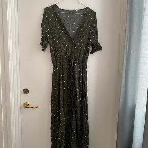 Grøn maxi-kjole med hvide prikker, har to lommer.