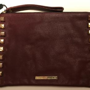 """Varetype: Clutch Størrelse: 21x28 cm Farve: Bordeaux Fast pris  Lækker clutch i læder. Nitterne er lidt """"slået"""" så det giver det rå look. Aldrig brugt..."""